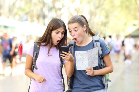 Surprised backpackers finding travel information in a smart phone in the street Stock Photo