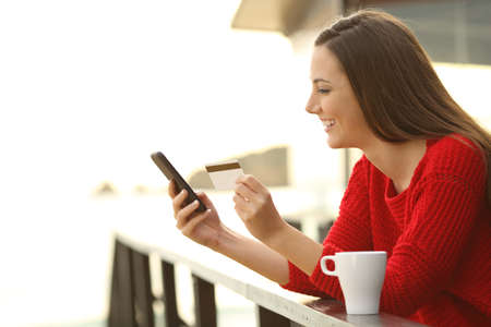 Hotel guest paying online with credit card and a smart phone from am hotel on the beach Stock Photo