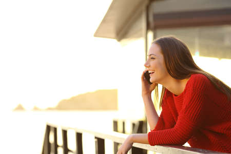 Side view portrair of a resort guest having a mobile phone conversation on vacation in an apartment on the beach