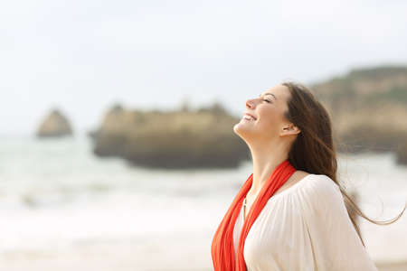 Mujer feliz respirando aire fresco en la playa Foto de archivo