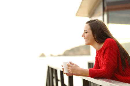Hotel guest contemplating beach holding a coffee cup in an apartment balcony