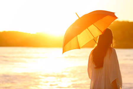 Back view portrait of a woman walking with an umbrella at sunset on the beach