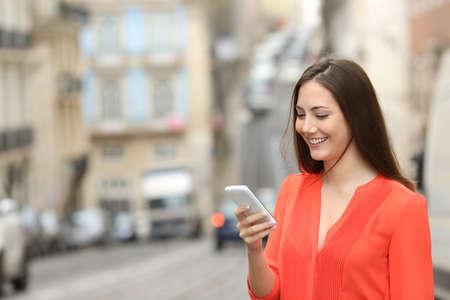 Happy woman in orange uses a smart phone walking in the street