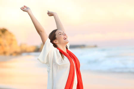 Excited woman celebrating sunset raising arms on the beach