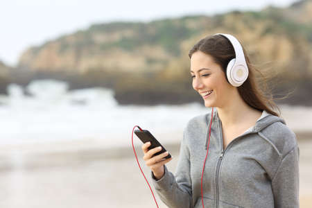 Happy teenage girl listening to music with headphones and a smart phone on the beach Stock Photo