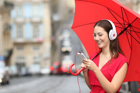 Happy woman listening to music with phone and headphones in a rainy day in the street