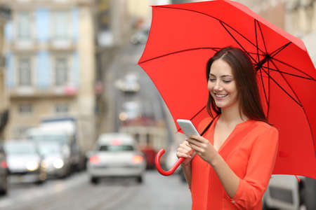 Happy woman using a smart phone holding an umbrella under the rain in the street