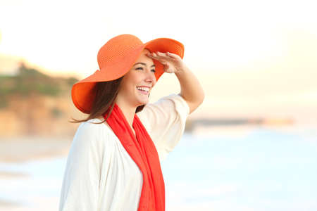 Happy woman scouting in the beach with hand on forehead with the sea in the background