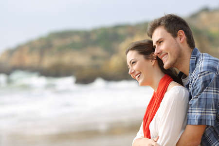Side view portrait of a happy couple hugging and looking at horizon on the beach 스톡 콘텐츠