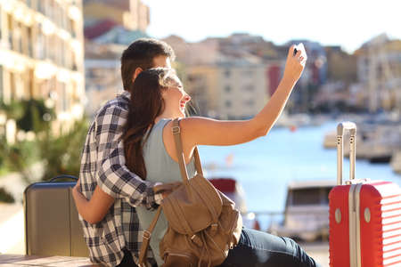 Happy tourists takig selfies sitting in a port on summer vacation