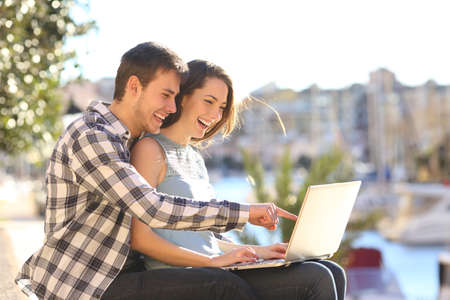 Happy couple using a laptop sitting in a port on summer vacation
