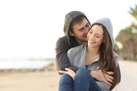 Front view portrait of a happy couple of teens flirting on the beach Foto de archivo - 107904276