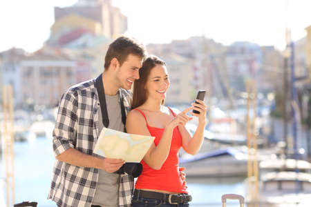 Happy couple of tourists checking online information in a smart phone on vacation Stock Photo