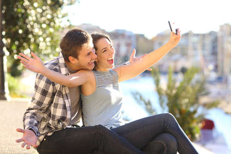 Funny couple taking selfies with a smart phone outdoors on summer vacation