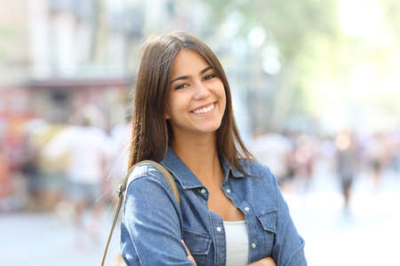 Portrait of a beautiful teen posing looking at camera with perfect smile in the street