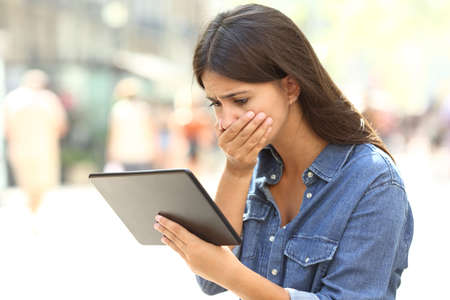 Worried girl reading online news in a tablet in the street