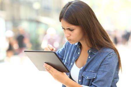 Chica enojada que tiene problemas en línea con una tableta en la calle