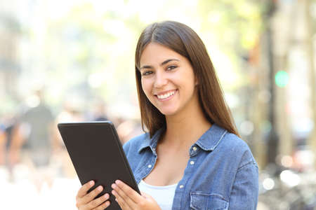 Happy girl posing looking at camera holding a tablet in the street Stock Photo