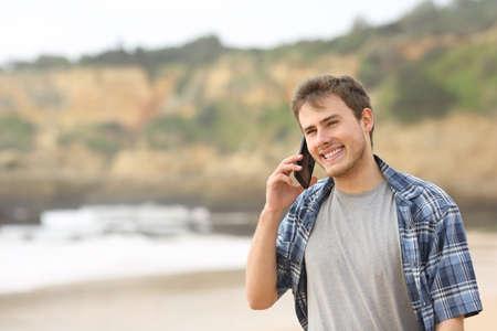 Happy teenage guy talking on mobile phone walking on the beach