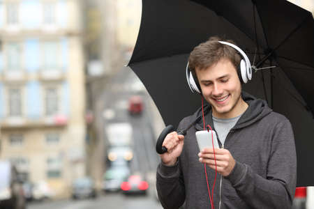 Happy teen listening to music with a smart phone and headphones under the rain in the street 스톡 콘텐츠