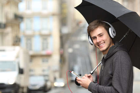Happy teen listening to music wearing headphones looking at you in the street under the rain Stock Photo