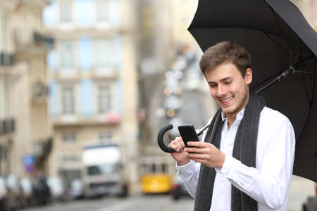 Happy man using a smart phone and holding an umbrella in a rainy day in the street