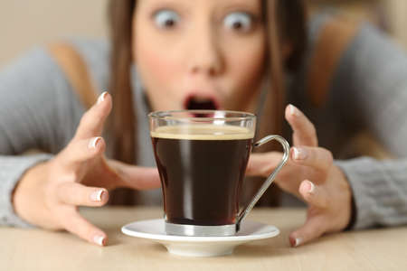 Front view portrait of an amazed woman looking at coffee cup Stock Photo