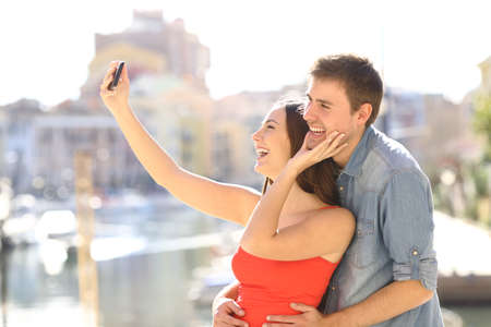 Happy couple of tourists taking selfies with a smart phone on summer vacation Stock Photo
