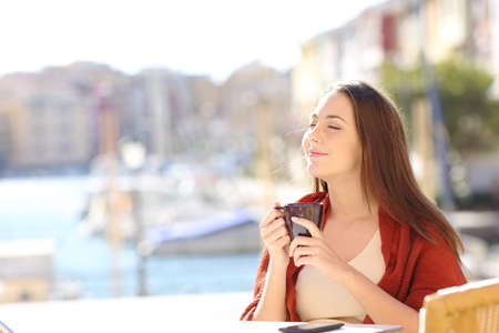 Happy woman enjoying a cup of coffee in a restaurant on vacation on the beach
