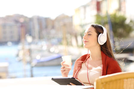Happy girl relaxing in a coffee shop listening to music with headphones and a tablet on vacation