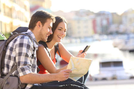Happy couple on vacation booking hotel online with a smart phone