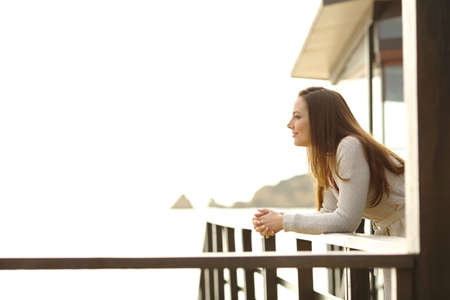 Side view portrait of a pensive hotel guest contemplating ocean from a balcony on the beach