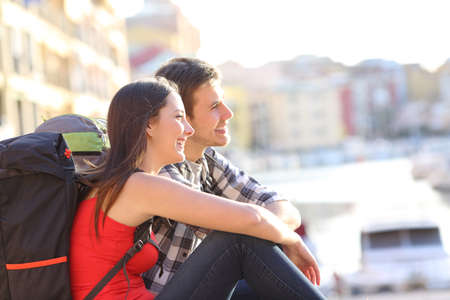 Happy couple of backpackers sightseeing on summer vacation
