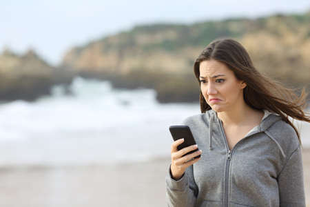 Disappointed teen reading phone message and grimacing walking on the beach