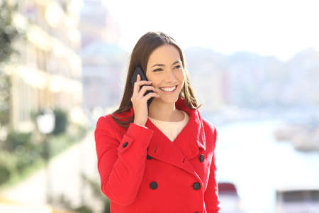 Happy woman in red talking on phone in winter in a coast town street