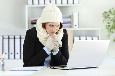Kalte verärgerte Führungskraft, die im Büro mit einem Heizungsausfall im Winter arbeitet