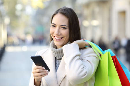 Happy shopper holding a smart phone and colorful shopping bags in winter in the street Stock Photo