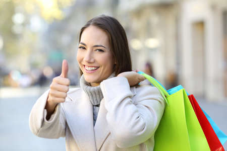 Happy shopper with thumbs up holding shopping bags in winter in the street Stock Photo