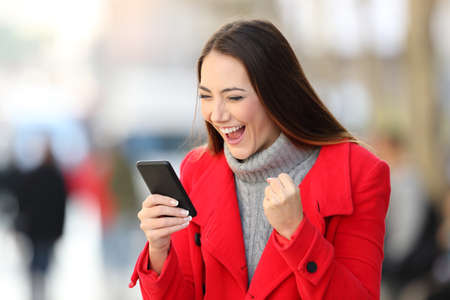 Portrait of an excited woman in red reading good news in a smart phone in winter on the street