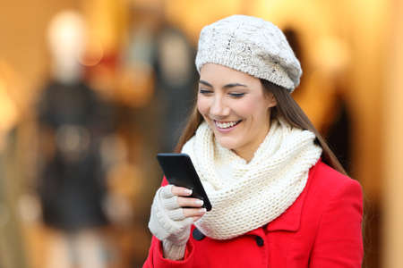 Portrait of a fashion girl wearing a red coat using a phone on a street in winter with a storefront in the background