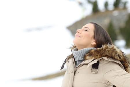 Happy lady breathing fresh air on winter holiday in a cold snowy mountain Standard-Bild - 108745819
