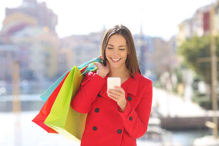 Front view portrait of a happy shopper tourist using a smart phone holding shopping bags in winter holiday Stock Photo