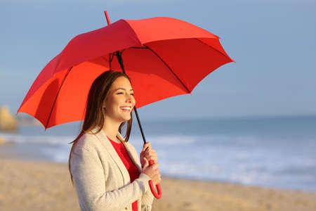Glückliches Mädchen mit dem roten Regenschirm, der Sonnenuntergang oder Sonnenaufgang am Strand beobachtet