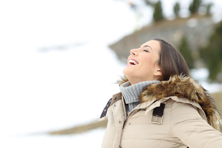 Happy woman breathing fresh air in winter holiday in the snowy mountain Stock fotó