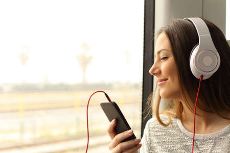 Happy commuter traveling into a train listening to music with a smart phone and headphones Imagens