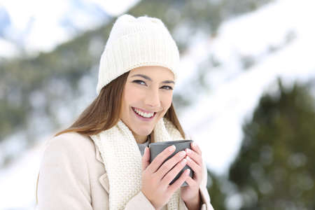 Happy girl posing holding a coffee mug in winter in a snowy mountain