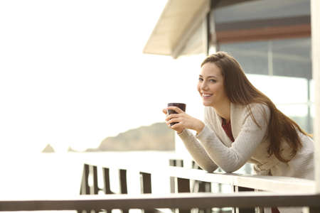 Happy hotel guest holding a coffee cup looking at you from a balcony on vacation Stock Photo
