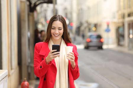 Portrait of a happy lady using a smart phone in winter walking in the street
