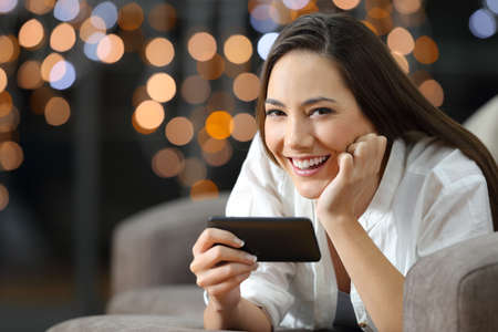 Girl holding a smart phone looking at camera in the night lying on a couch in the living room at home Stock Photo