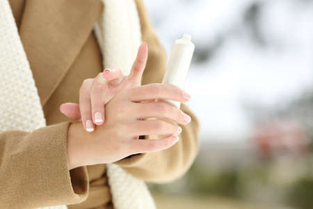 Close up of a woman hands rubbing applying moisturize cream in winter in a snowy mountain